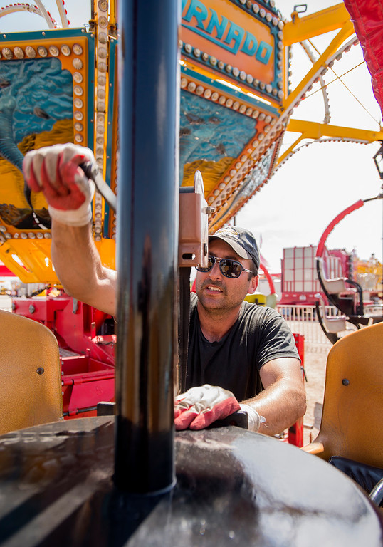 . Daniel Broch, from San Angelo, Texas, sets up a ride for the Carnival Americana Wednesday afternoon August 3, 2016 during the Larimer County Fair and Rodeo at The Ranch in Loveland. (Photo by Michael Brian/Loveland Reporter-Herald)