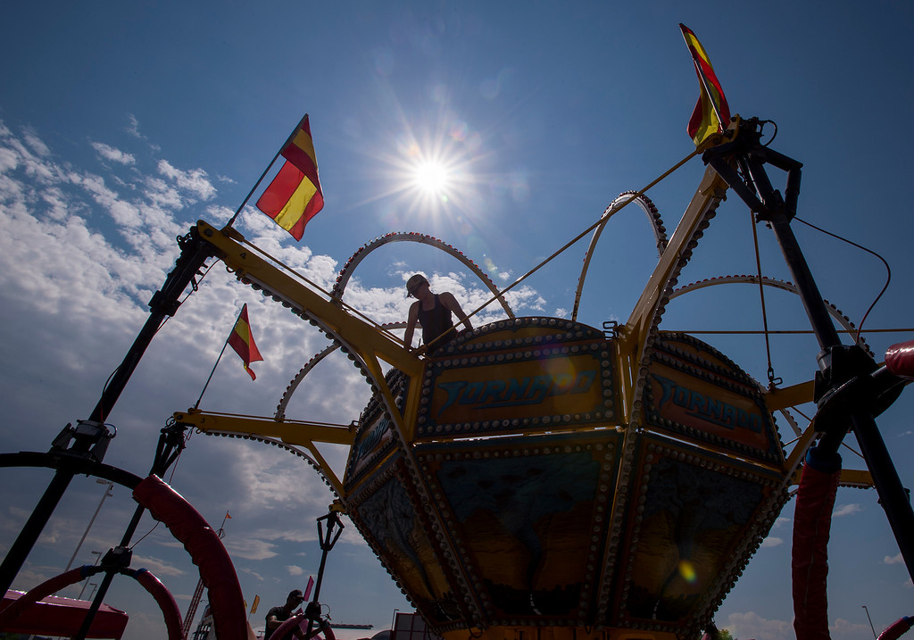 . Keely Williams, with Williams Amusement Rides, works up high Wednesday afternoon August 3, 2016 setting up a ride for the Larimer County Fair and Rodeo at The Ranch in Loveland. The Carnival Americana will open at 4 p.m. Friday August 5 and run through Tuesday August 9, 2016. (Photo by Michael Brian/Loveland Reporter-Herald)