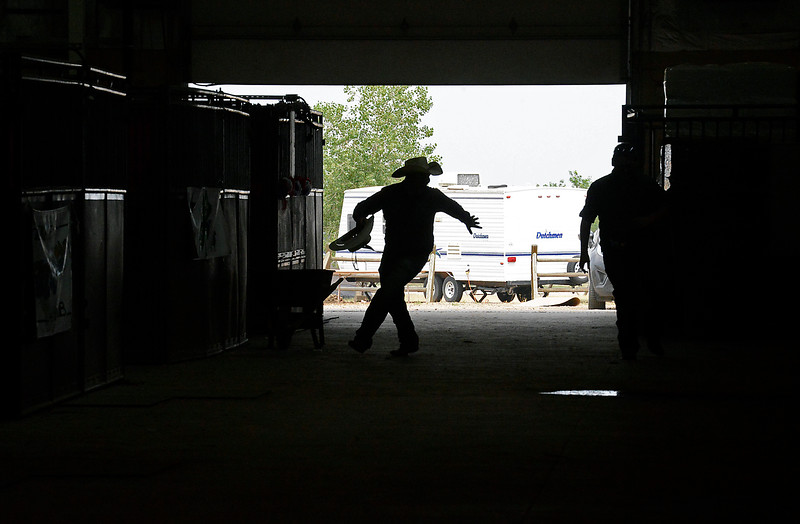 Colton Harris of Loveland is silhouetted in the horse barn as he steals his friend, Daniel Starks' cowboy hat and runs on Tuesday, Aug. 2, 2016, during the Larimer County Fair at The Ranch in Loveland.  (Photo by Jenny Sparks/Loveland Reporter-Herald)