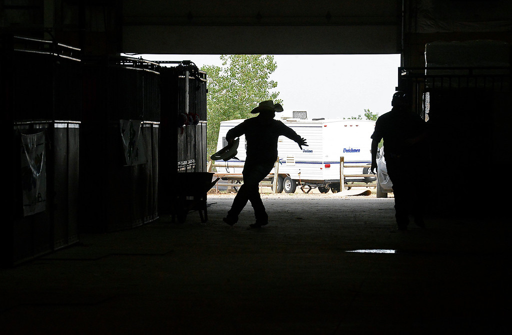 . Colton Harris of Loveland is silhouetted in the horse barn as he steals his friend, Daniel Starks\' cowboy hat and runs on Tuesday, Aug. 2, 2016, during the Larimer County Fair at The Ranch in Loveland.  (Photo by Jenny Sparks/Loveland Reporter-Herald)