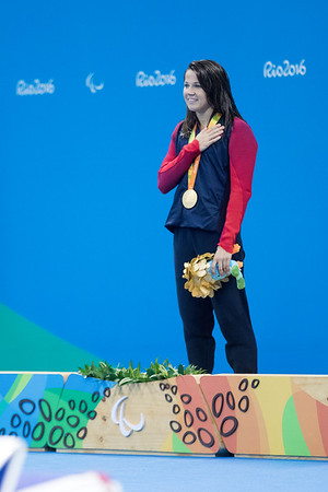 Her second gold medal as she listens to the Star Spangled Banner being played as the US flag is raised.