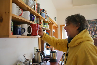 IMG_3082 coleen O'Connell gets her mug from a rack shared by other residents in the common house kitchen