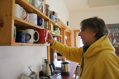 IMG_3082 coleen O'Connell gets her mug from a rack shared by other residents in the common house kitchen copy