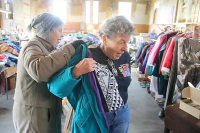 IMG_3469 volunteer nancy pedrick helps linda crowe of east thetford try on coat
