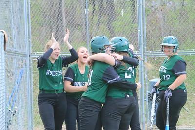 Elizabeth Fitzpatrick,  Hannah Reali at left, as maddie moore hugs Loretta Blakeney as she crosses home base on her two run home run