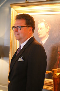 IMG_6972 gary thulander, the president and general mananger of Woodstock Resort Corporation, poses in front of Laurence Rockefeller portrait in library