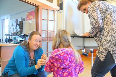 IMG_4622 town clerk Becky Fielder gives a sticker to joleigh hewitt,3, while her mom karen votes