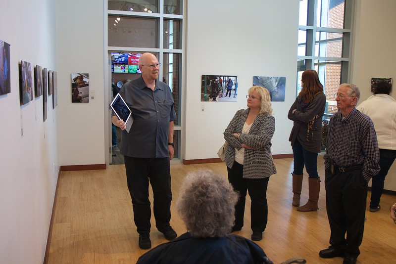 Dr. Bob Carey guides individuals through his photography exhibit in the Tucker Art Gallery.