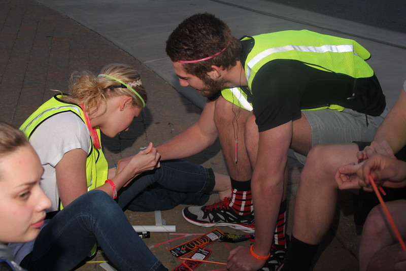 Photo by Tessa Walsh Carol Zangla helping Jake Ennis put on glow bracelets prior to the race
