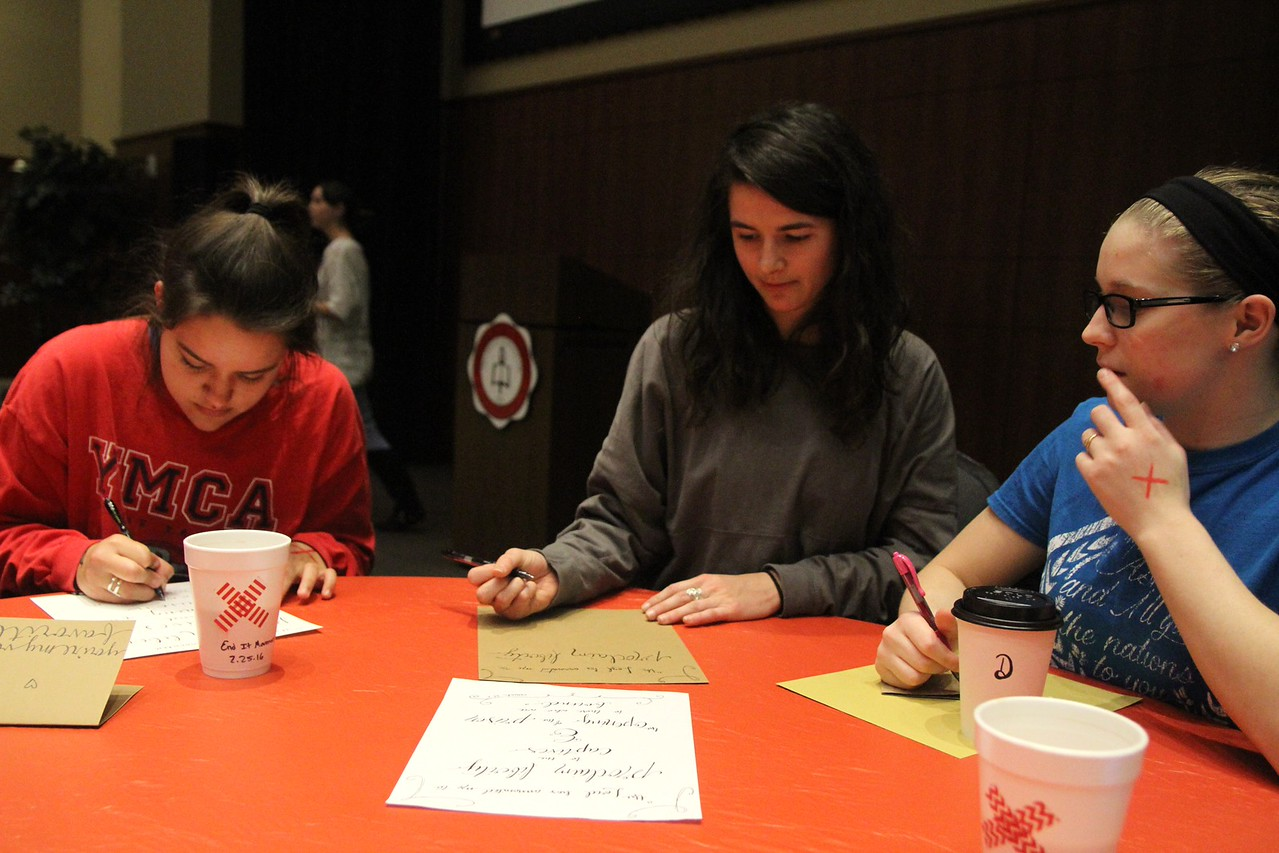 Release president Mary Toohey works on her calligraphy with friends Austyn Gorski and Tessa Walsh.