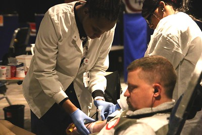 An American Red Cross employee drawing blood from a local donor.