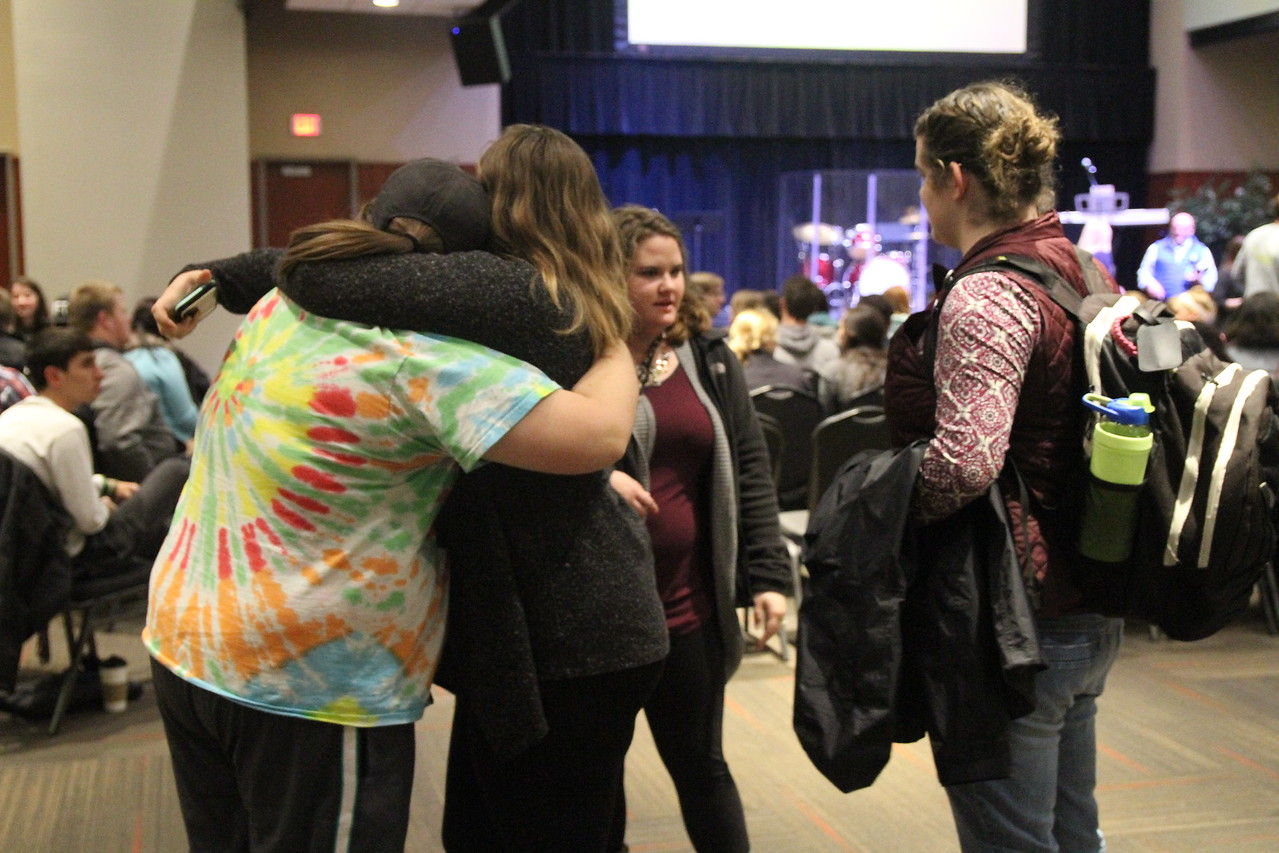 Shelby Robinson and Caitlyn Brotherton hug while Michelle Evans and Taylor Swain talk before Tuesday night's celebration week event started.