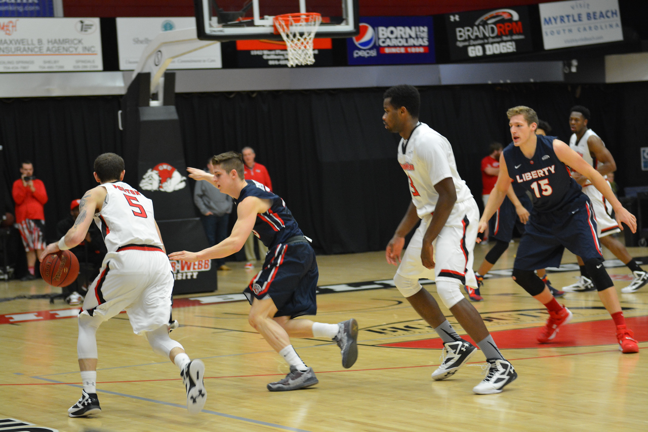Dylan Poston heading towards the basketball with the ball.