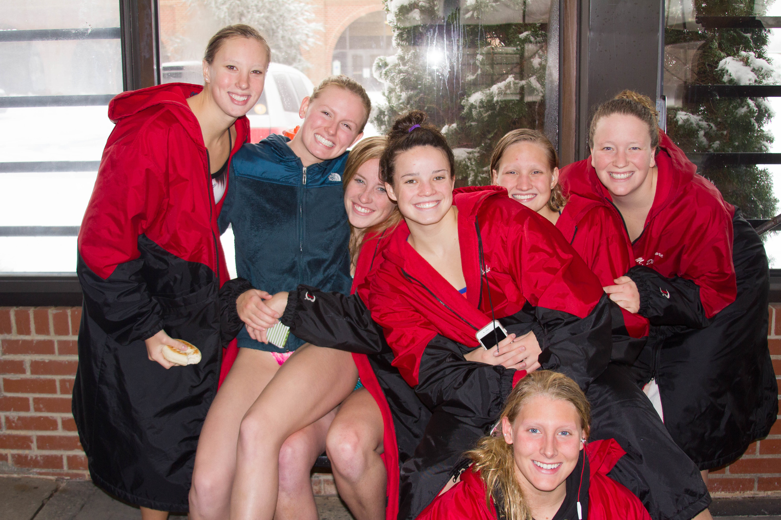 Photo by Adel Kiss Christiana Clayton, Carol Zangla, Hope Saunders, Lauren Oglesby, London Schumacher, Madi Dinsmore and Morgan VanderScaaf. Resting after workout and before team relays. The swim team love their parkas for staying warm, even when wet.