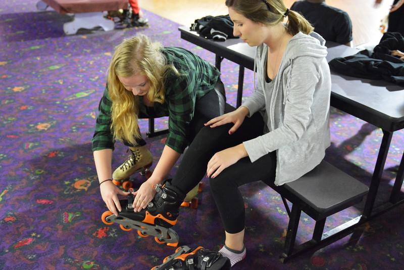 Mikayla Wess helping friend Lauren Eisenbath get her skates on.