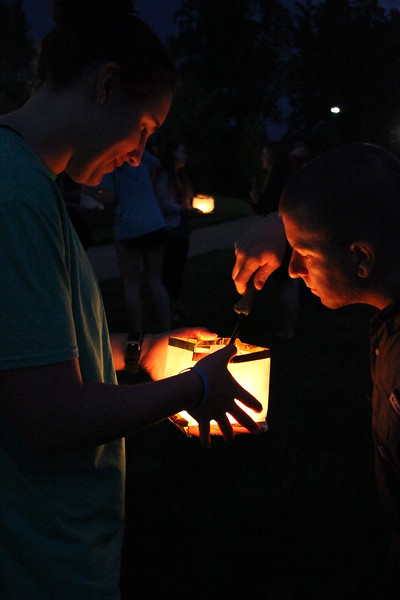 Micah Martin lights Taylor Schwartz's lantern for her.