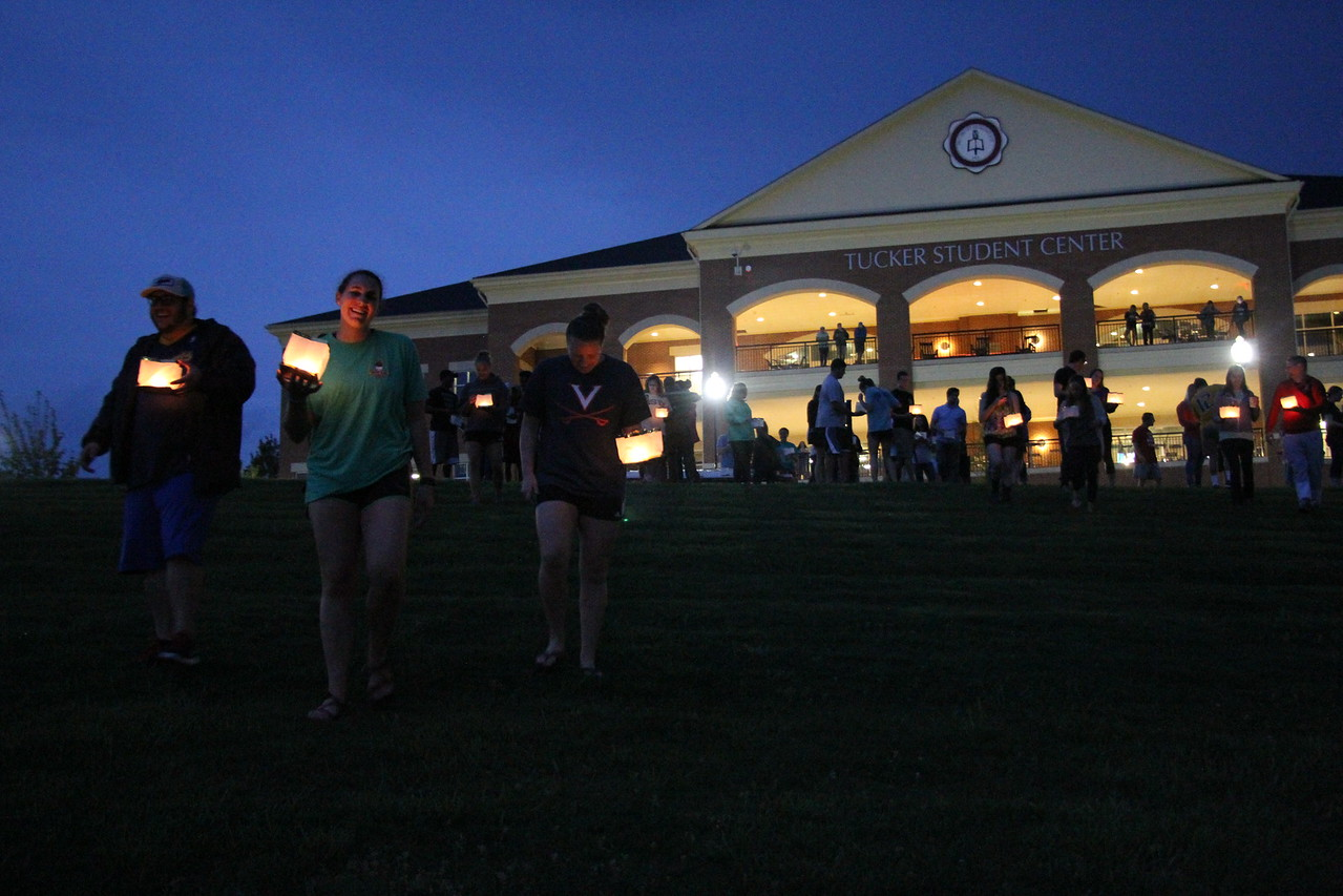 Students walk down to the lake with their lanterns.
