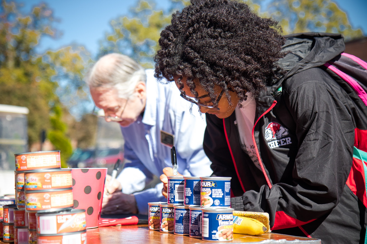 Students are invited to write an encouraging message on canned goods to be donated to local are homeless shelters and food banks.