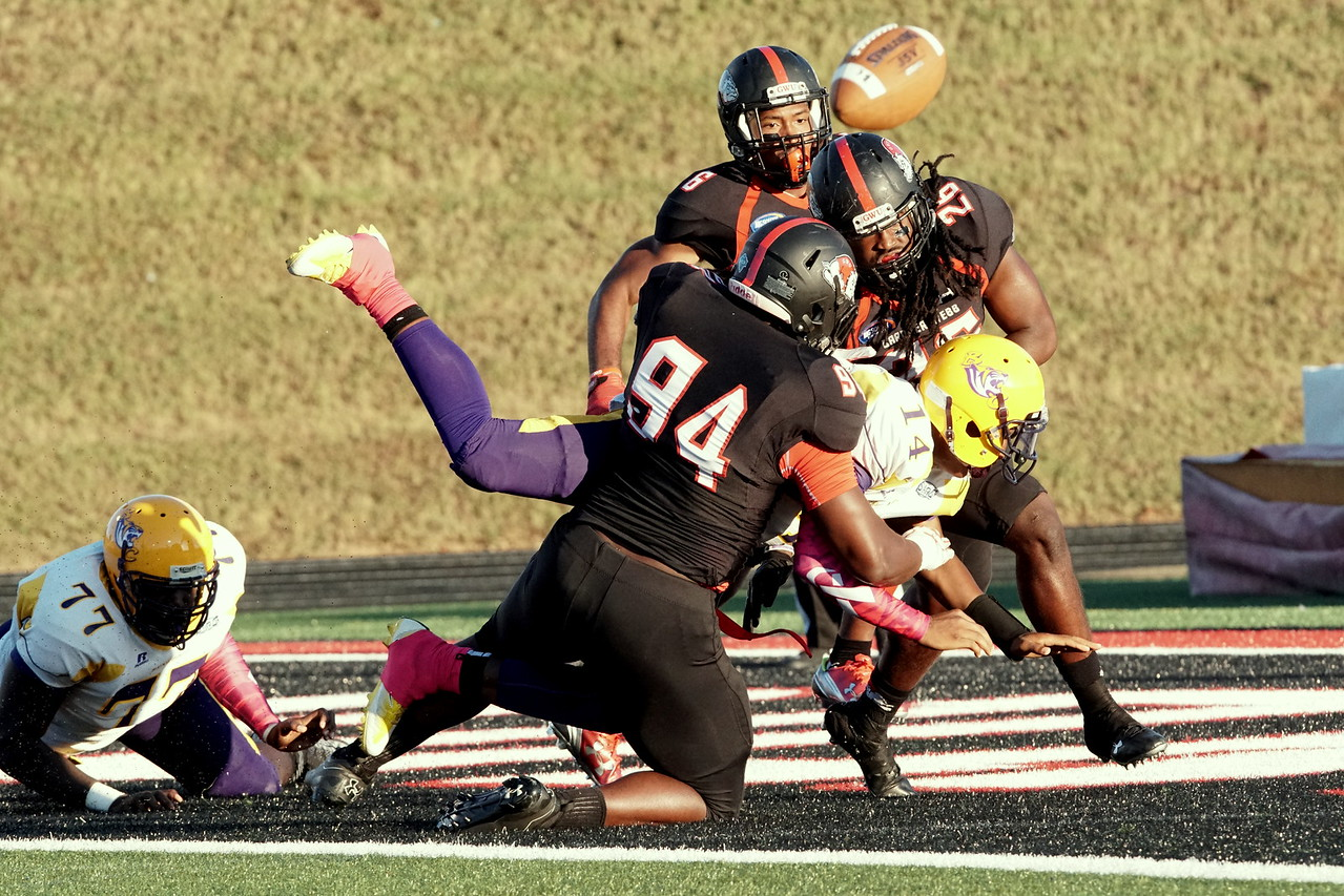 Laron Glenn, Aaron Cook, and Thomas Adams tackle the ball from Benedict.-Taken by Ashley Falls