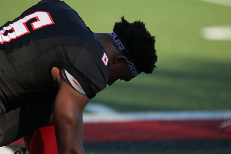 Before the game, #6, Thomas Adams, kneels to pray.