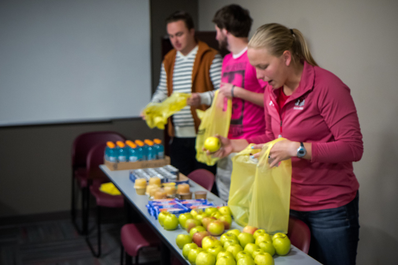 Students prepare bags for backpacks of food and snacks for local area school children.