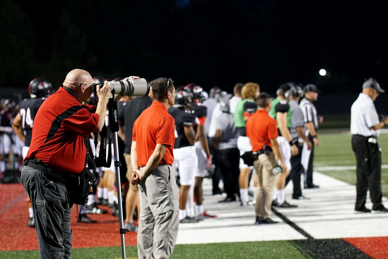 Bob Carey takes photographs of the football game.
