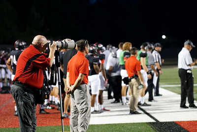 Bob Carey takes photographs of the football game.