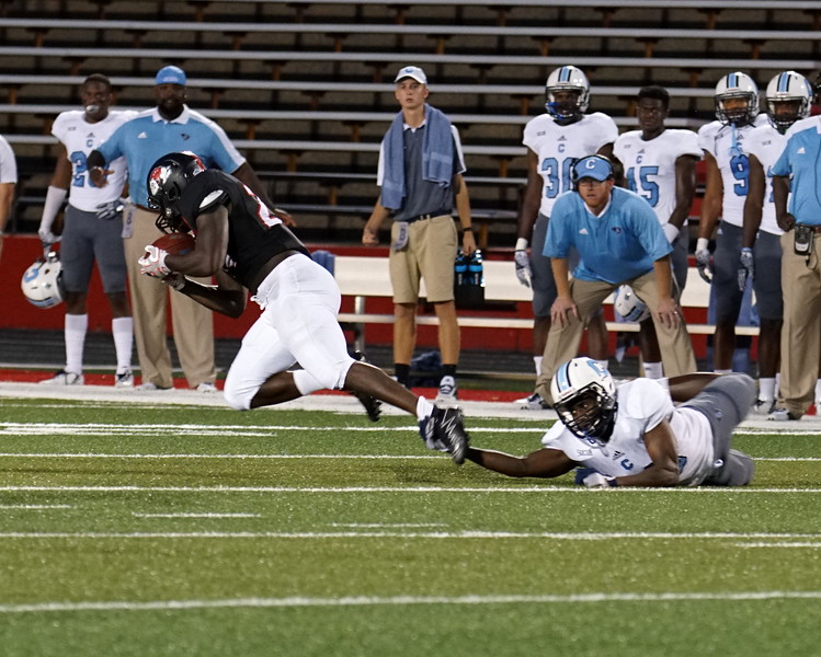 A Citadel player grabs a bulldog's foot.