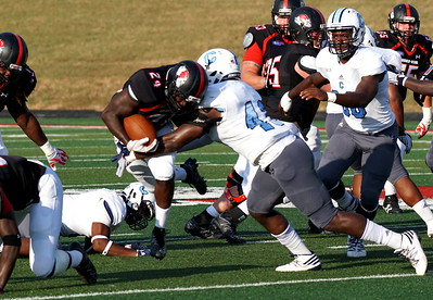 Number 24, Khalil Lewis, is tackled by the Citadel player Tevin Floyd.