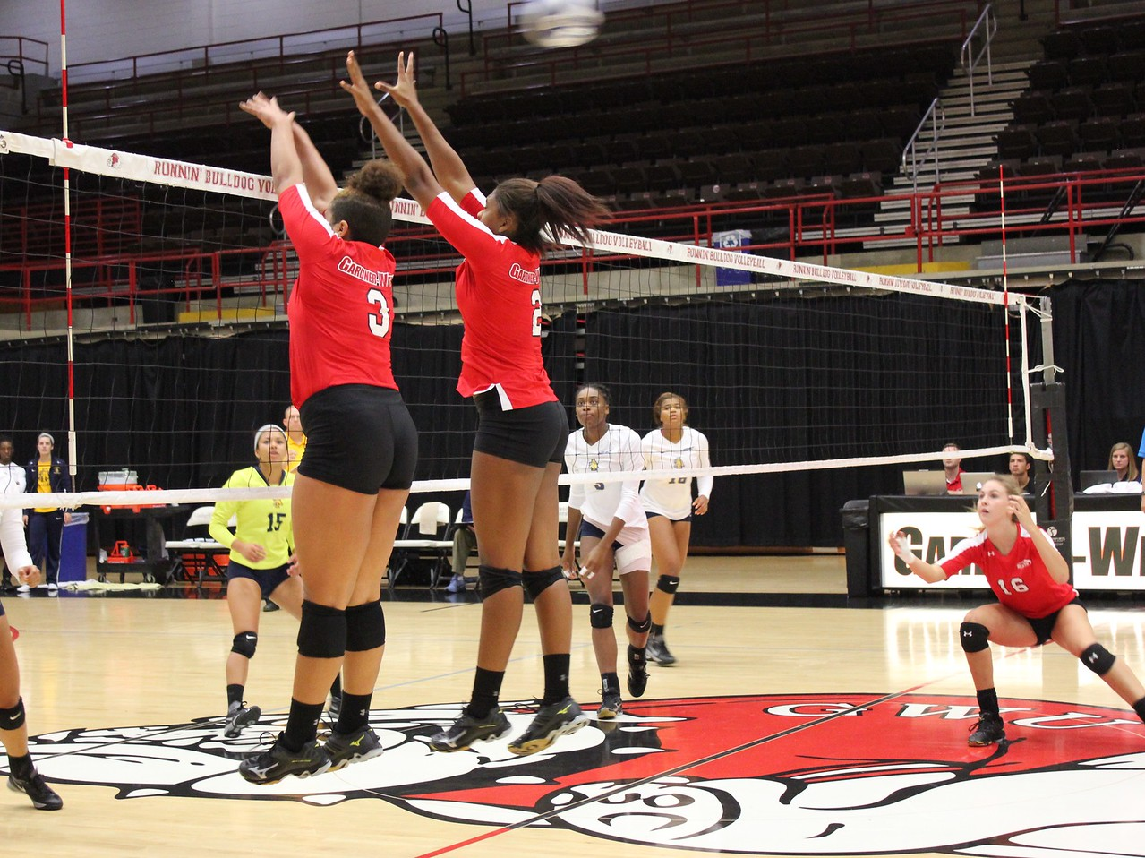 Taylor Lillard (3) and Kaelyn Dyson (2) block as Molly Johnston (16) prepares to get the tipped ball