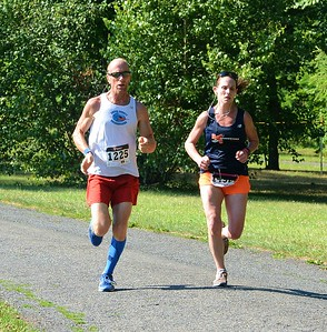First female finisher Allyson Thompson, (right) of Holland, keeps pace with Newtown's Richard Kanak (1225).