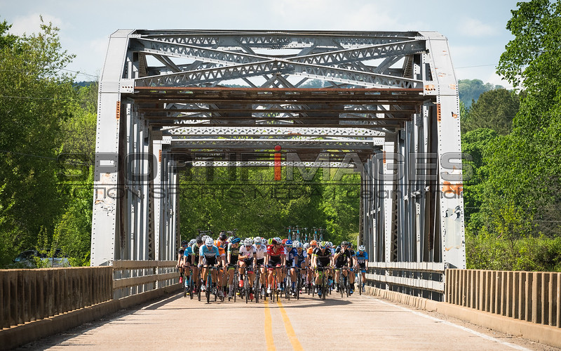 "Joe Martin Stage Race. Stage 2. UCI Pro 1 Men. The field is rolling across a steel girder bridge in the Arkansas countryside while a breakaway is working hard establishing a lead which will eventually swell up to 5' 55""."