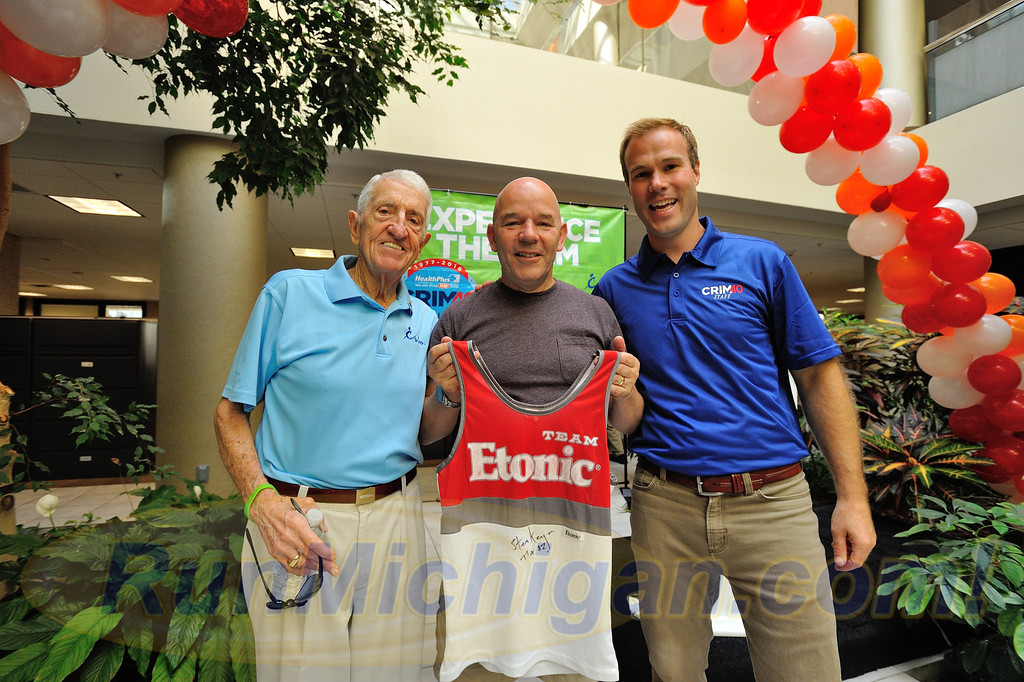 Original race co-founder and director Bobby Crim (left), first ever 10 Mile Race overall champion Steve Kenyon (center) and current Crim Race Director Andrew Younger, pose with Kenyon's original race singlet, worn during his 1977 victory. (Photo: RunMichigan.com)