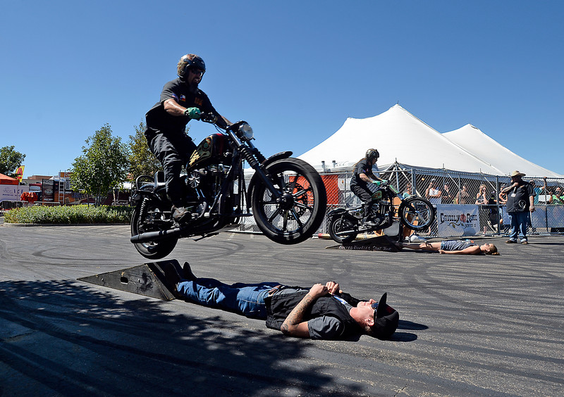 "Stunt riders Eric Rocks, left, and Tony ""King Tony"" Jones, right, jump over audience members on their Harley Davidson motorcycles Monday, Sept. 5, 2016, during the Busted Knuckles Stunt Show at Thunder in the Rockies Bike Rally in Loveland. The audience members, Joel Artzer, left, and Beth Gilbert, said it was awesome to have the bikes fly over them. (Photo by Jenny Sparks/Loveland Reporter-Herald)"