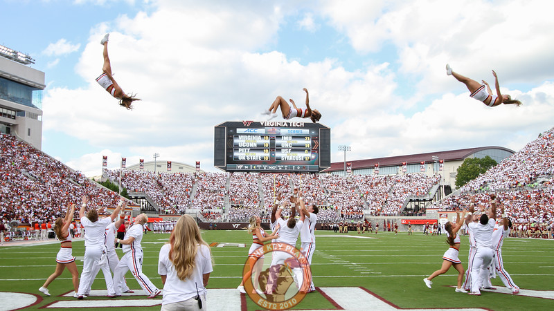 Virginia Tech cheerleaders perform a synchronized flip during a media timeout. (Mark Umansky/TheKeyPlay.com)