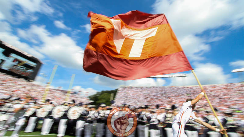 A Virginia Tech cheerleader runs onto the field carrying a VT logo flag. (Mark Umansky/TheKeyPlay.com)