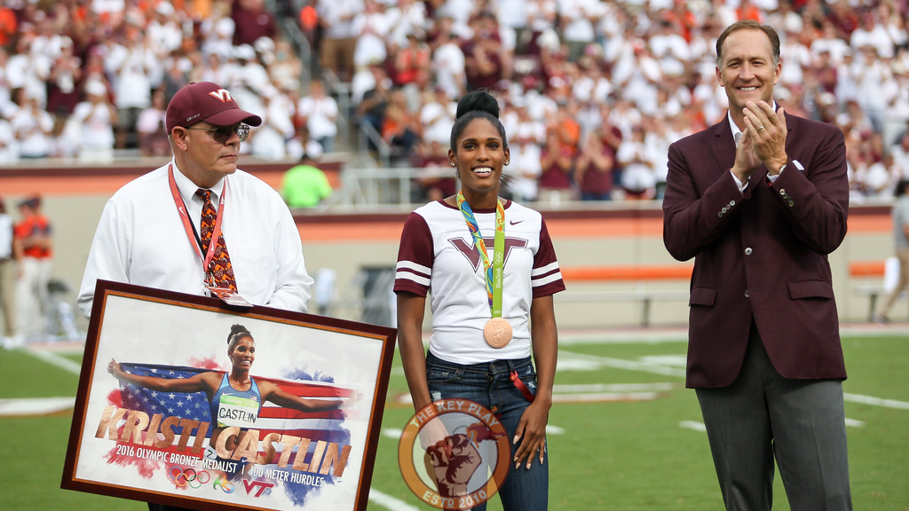 Former Virginia Tech hurdler and Rio 2016 bronze medalist Kristi Castlin (center) is honored by track and field coach Dave Cianelli (left) and Virginia Tech athletic director Whit Babcock (right) during a media timeout. (Mark Umansky/TheKeyPlay.com)