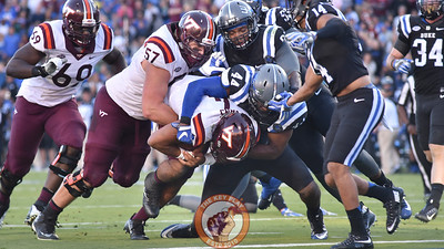 Virginia Tech offensive lineman Wyatt Teller (57) carries quarterback Jerod Evans (4) across the goal line for a touchdown. (Michael Shroyer/TheKeyPlay.com)