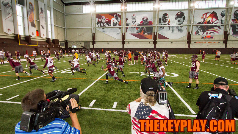 The Hokies warm up inside the Beamer Barn for the first fall practice of the year. (Mark Umansky/TheKeyPlay.com)