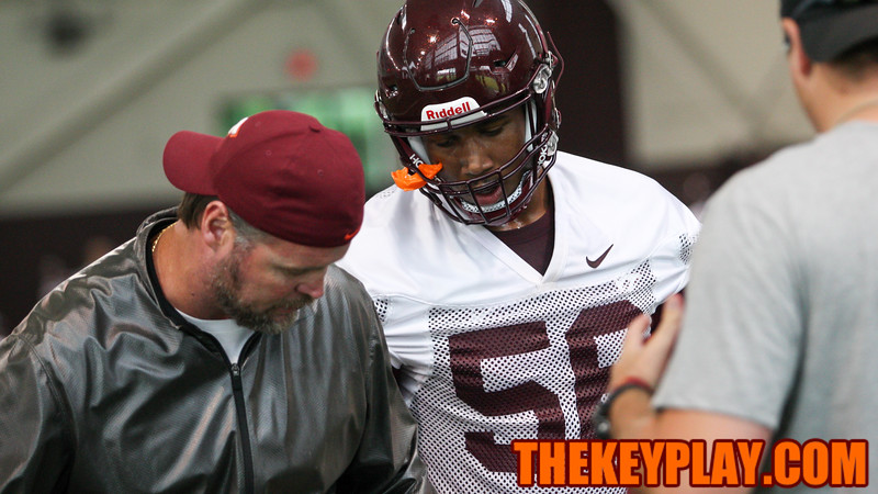 OL coach Vance Vice shows T.J. Jackson proper footwork during group drills. (Mark Umansky/TheKeyPlay.com)