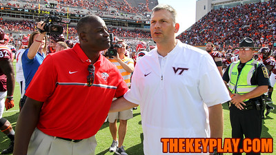 Virginia Tech head coach Justin Fuente (right) speaks with Liberty head coach Turner Gill (left) after the final whistle. (Mark Umansky/TheKeyPlay.com)