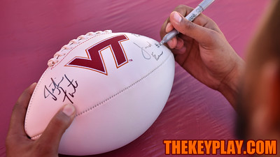 Quarterback Jerod Evans signs his name on a VT logo football. (Michael Shroyer/ TheKeyPlay.com)