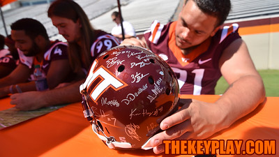 Defensive tackle Steve Sobczak adds his name to a helmet containing several Hokies' signatures. (Michael Shroyer/ TheKeyPlay.com)