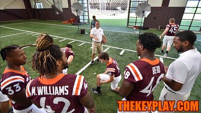 HokieSports photographer Dave Knachel arranges the running backs for their group photo. (Michael Shroyer/ TheKeyPlay.com)