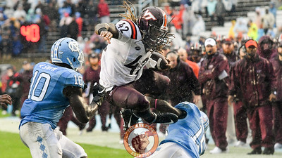 Virginia Tech running back Marshawn Williams (42) leaps over North Carolina safety Donnie Miles (15). (Michael Shroyer/ TheKeyPlay.com)