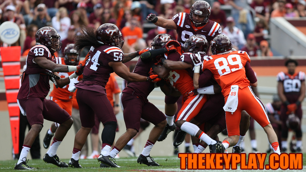 WR Divine Deablo is gobbled up by a swarm of defenders after a short catch. (Mark Umansky/TheKeyPlay.com)