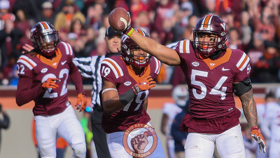 Andrew Motuapuaka (54) holds up the ball after intercepting a UVa pass. (Mark Umansky/TheKeyPlay.com)