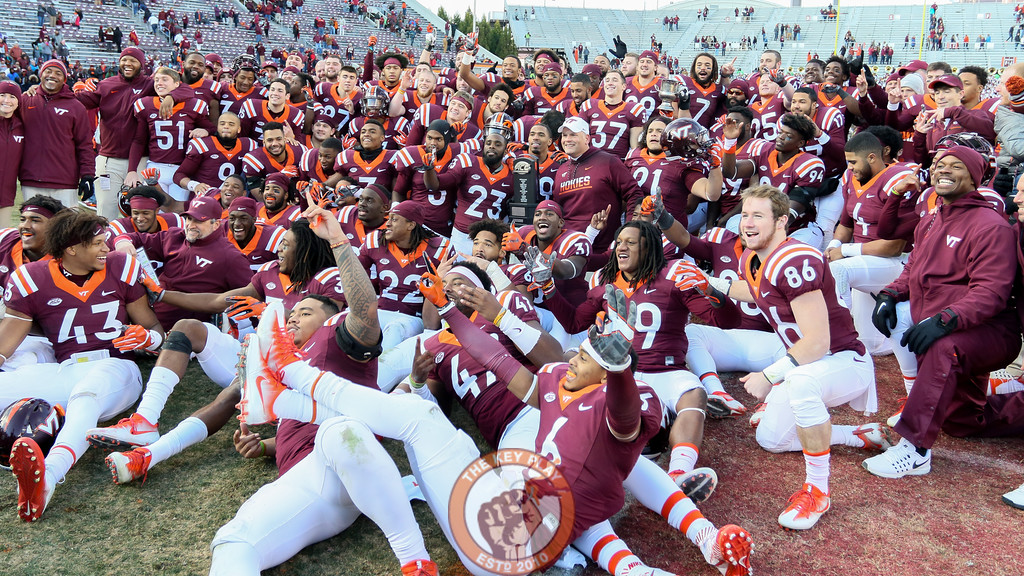 The Hokies pose with the ACC Coastal Division Champion trophy on Worsham Field at Lane Stadium after defeating UVa in the final regular game of the season. (Mark Umansky/TheKeyPlay.com)