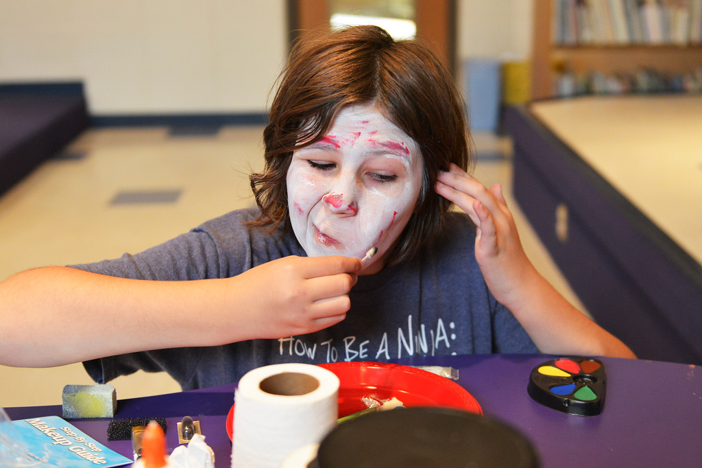Justin Sheely | The Sheridan Press<br /> Ten-year-old Valerie Kurtz puts makeup on her face during the Tween Zombie Fest last October at the Sheridan County Fulmer Public Library.