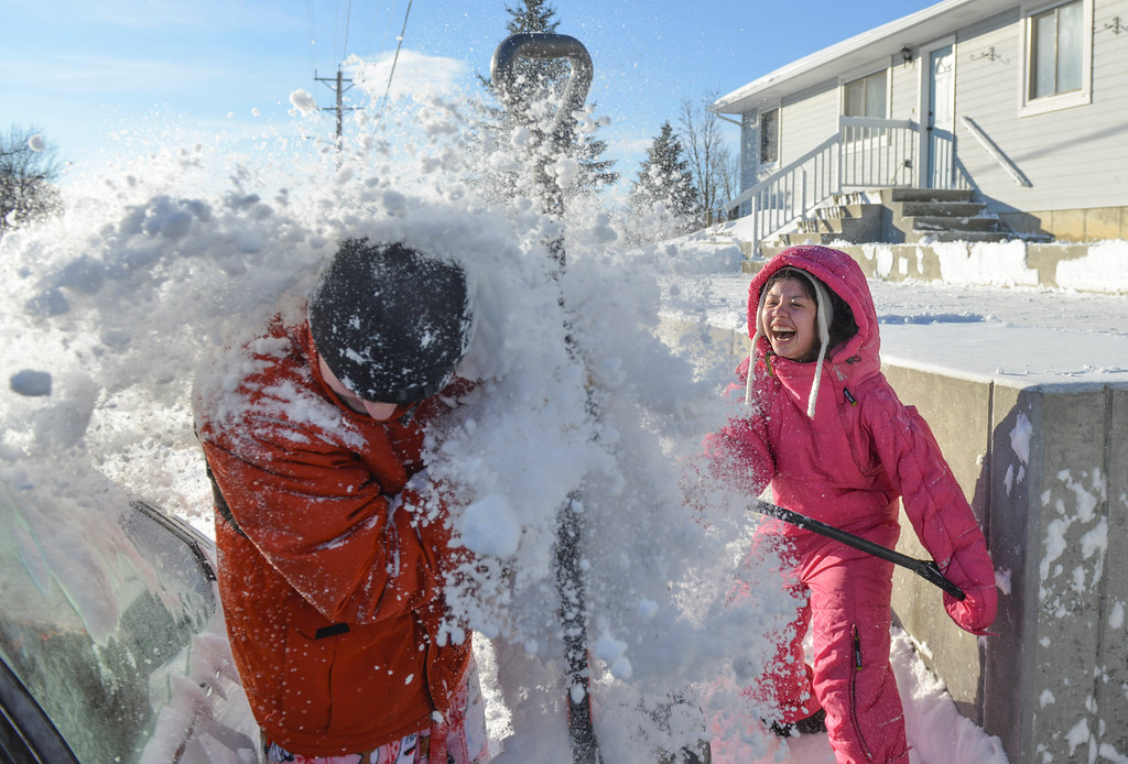 Justin Sheely | The Sheridan Press<br /> Gaby Reyes spills a shovel full of snow on her boyfriend Jonathan Ruhoff the day after Christmas in Sheridan. A winter blizzard dumped 5 to 7 inches of snow in the city of Sheridan over Christmas Day. Story reported up to 12 inches of snow.